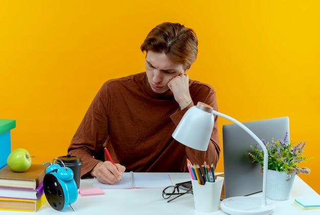 Myślenie młody uczeń chłopiec siedzi przy biurku z narzędzi szkolnych, pisząc coś na notebooku na żółto