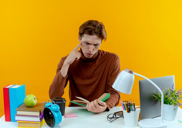 Myślenie młody uczeń chłopiec siedzi przy biurku z narzędzi szkolnych, trzymając i patrząc na książkę kładąc rękę na brodzie na żółto