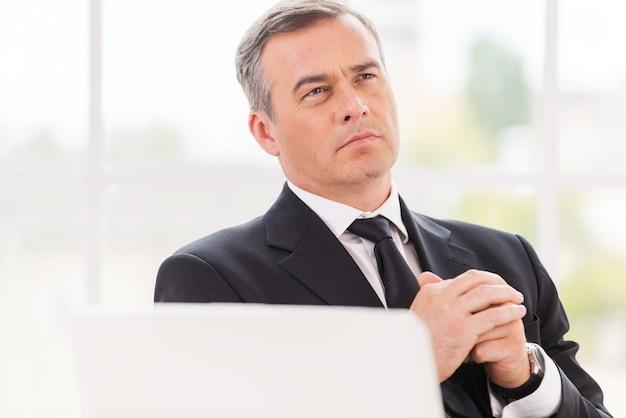 Myślenie o biznesie. rozważny dojrzały mężczyzna w formalnym stroju, trzymający splecione ręce i odwracający wzrok, siedząc w swoim miejscu pracy