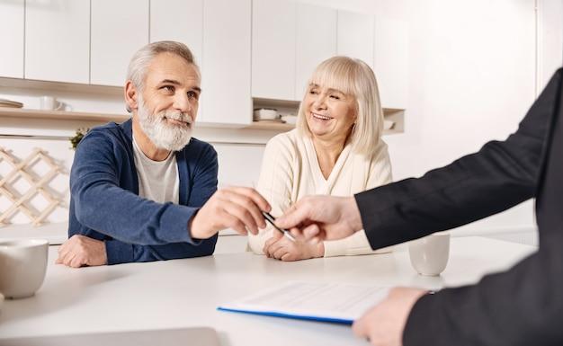 Myślenie o naszej przyszłości. uśmiechnięty zadowolony starsza para siedzi w domu i rozmawia z doradcą finansowym podczas podpisywania umowy