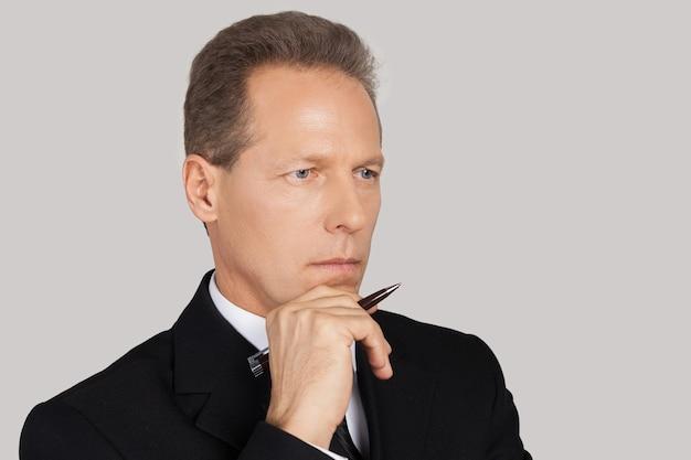 Myślenie o nowych możliwościach. pewny siebie dojrzały mężczyzna w formalnej odzieży, pracujący na laptopie, stojący na szarym tle