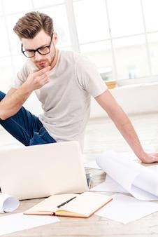 Myślenie o nowym projekcie. rozważny młody człowiek bada plan, siedząc na podłodze w domu
