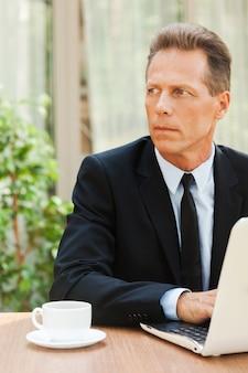 Myślenie o rozwiązaniach. rozważny dojrzały mężczyzna w formalnym stroju odwracający wzrok, siedzący przy stole z laptopem na nim
