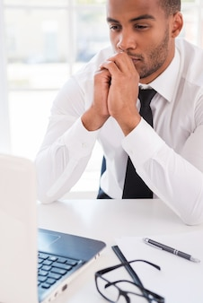 Myślenie o rozwiązaniu. rozważny młody afrykanin w koszuli i krawacie patrzący na swojego laptopa