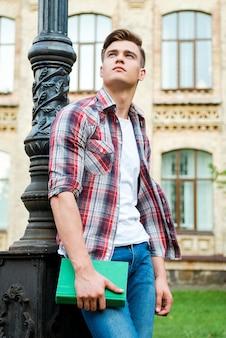 Myślenie o świetlanej przyszłości. niski kąt widzenia zamyślonego studenta mężczyzny trzymającego książkę i patrzącego w górę stojącego przed budynkiem uniwersyteckim