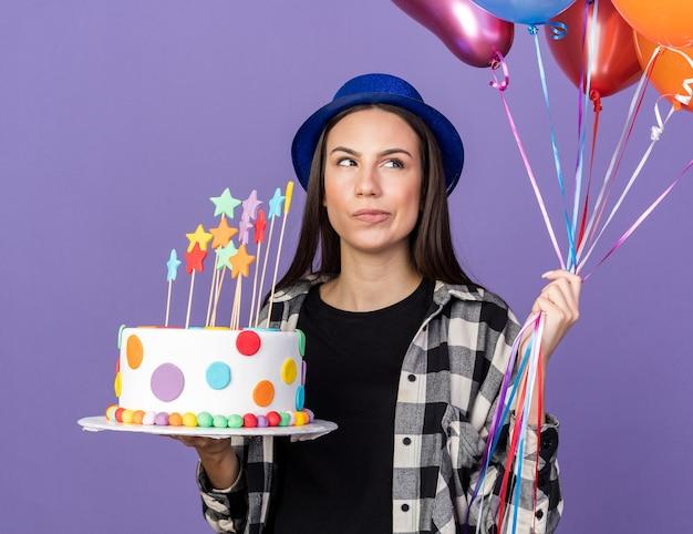 Myślenie patrząc na bok młoda piękna dziewczyna w imprezowym kapeluszu trzymająca balony z ciastem