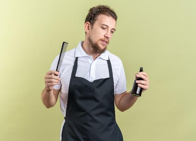Myślenie, patrząc w dół, młody męski fryzjer ubrany w mundur, trzymający butelkę z rozpylaczem z grzebieniem na białym tle na oliwkowo-zielonym tle