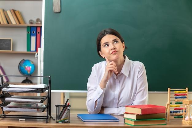 Myślenie, patrząc w górę, kładąc rękę na policzku, młoda nauczycielka siedzi przy stole z szkolnymi narzędziami w klasie