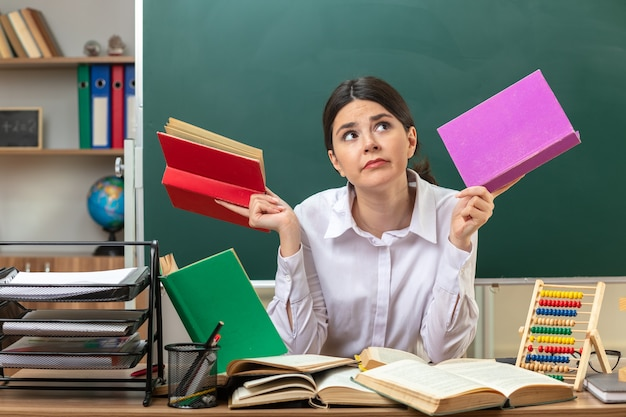 Myślenie patrząc w górę młodej nauczycielki trzymającej książkę siedzącą przy stole z narzędziami szkolnymi w klasie