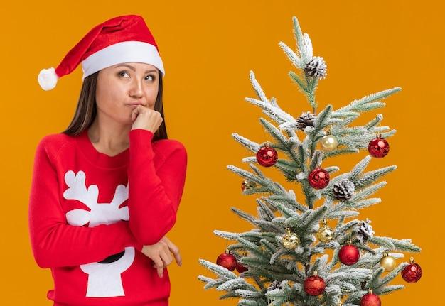 Myślenie patrząc z boku młoda azjatycka dziewczyna ubrana w świąteczny kapelusz ze swetrem stojący w pobliżu choinki kładąc dłoń na brodzie na białym tle na pomarańczowym tle