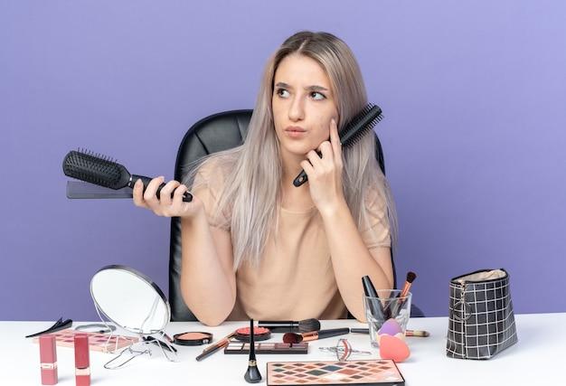 Myślenie patrząc z boku młoda piękna dziewczyna siedzi przy stole z narzędziami do makijażu, trzymając grzebienie na białym tle na niebieskim tle