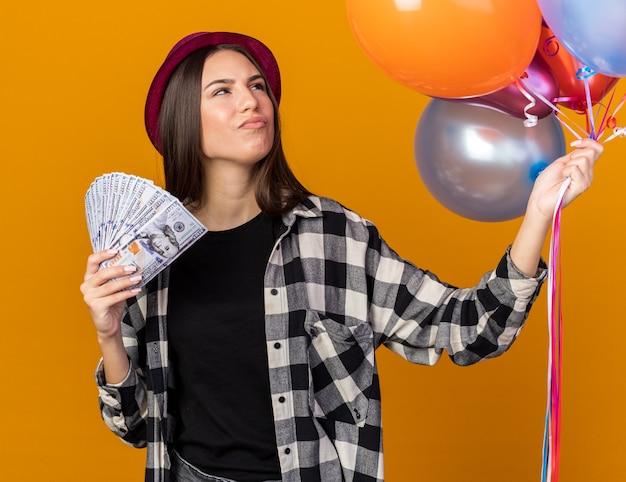 Myślenie patrząc z boku młoda piękna dziewczyna w kapeluszu imprezowym trzymająca balony z gotówką na białym tle na pomarańczowej ścianie