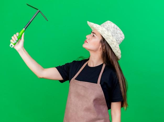 Myślenie piękna dziewczyna ogrodnik w mundurze na sobie kapelusz ogrodniczy podnosząc i patrząc na motyka grabie na białym tle na zielonym tle