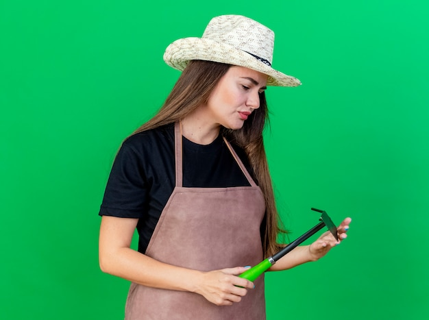 Myślenie piękna dziewczyna ogrodnik w mundurze na sobie kapelusz ogrodniczy trzymając i patrząc na motyka grabie na białym tle na zielonym tle