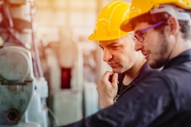 Myślenie pracownika, zespół serwisowy pracujący z maszyną razem praca zespołowa w fabryce przemysłu ciężkiego z kaskiem