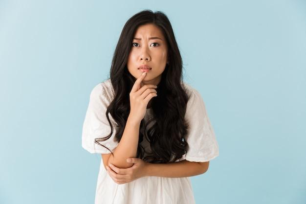Myślenie, przestraszony młody azjatycki piękna kobieta pozowanie na białym tle nad niebieską ścianą