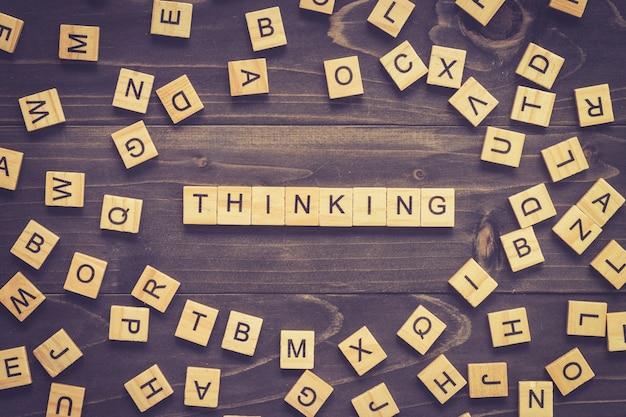 Myślenie słowo blok drewna na stole do koncepcji.