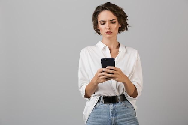 Myślenie zdezorientowana młoda biznesowa kobieta pozowanie na białym tle nad szarą ścianą za pomocą telefonu komórkowego i rozmowy