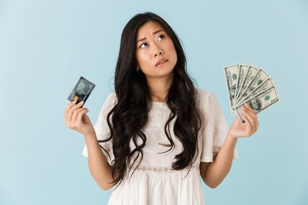 Myśli azjatycka piękna kobieta na białym tle nad niebieską ścianą, trzymając kartę kredytową i pieniądze