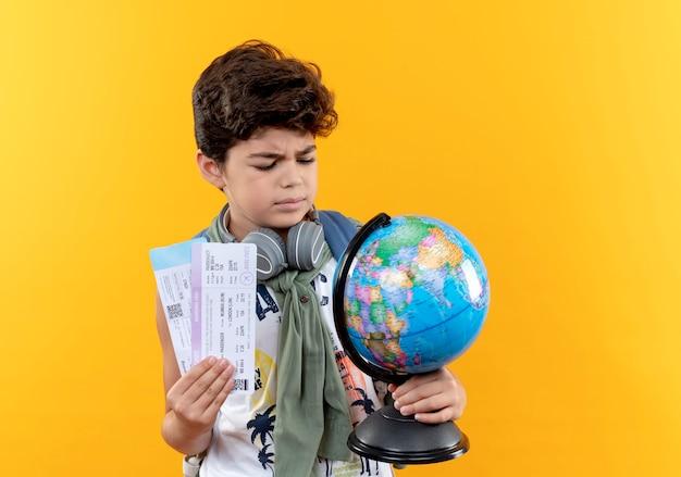 Myśli mały chłopiec w szkole noszenie plecaka i słuchawek, trzymając bilety i patrząc na kulę ziemską w ręku na żółto