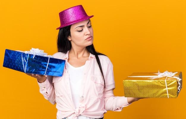 Myśli młoda piękna dziewczyna w kapeluszu imprezowym, trzymająca i patrząca na pudełka na prezenty izolowane na pomarańczowej ścianie