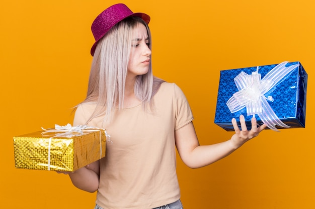 Myśli młoda piękna dziewczyna w kapeluszu imprezowym, trzymająca i patrząca na pudełka z prezentami