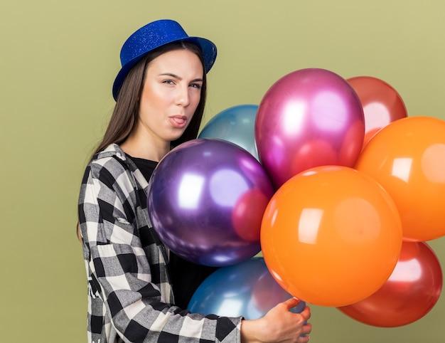 Myśli młoda piękna dziewczyna w niebieskim kapeluszu, trzymając balony