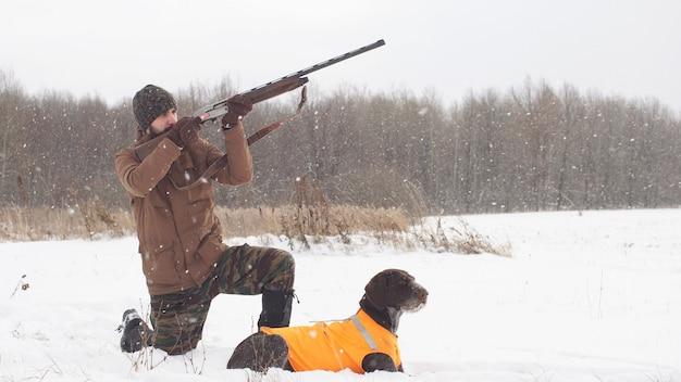 Myśliwy celuje w ptaka, a pies czeka na strzał. polowanie na hobby