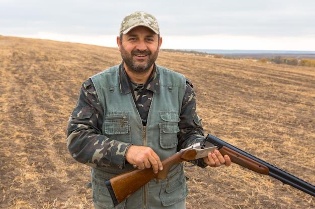 Myśliwy w kamuflażu z pistoletem podczas polowania na dzikie ptactwo lub zwierzynę łowną