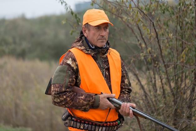 Myśliwy w kamuflażu z pistoletem podczas polowania na dzikie ptactwo