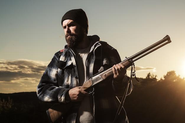 Myśliwy z pistoletem myśliwskim w lesie jesienią.