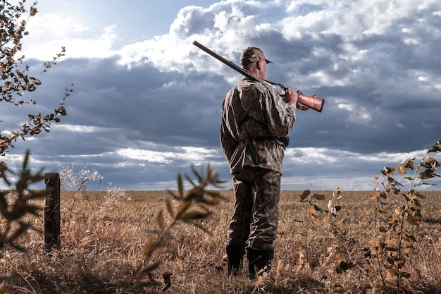 Myśliwy z pistoletem na ramieniu na tle pola. polowanie na dzikie zwierzęta. skopiuj miejsce