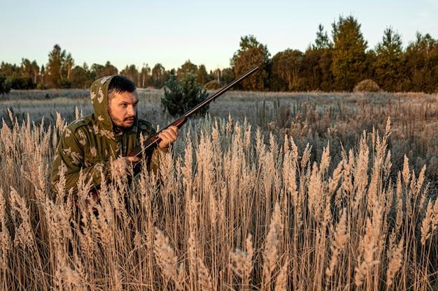 Myśliwy z pistoletem siedzi na trawie i czeka na zdobycz