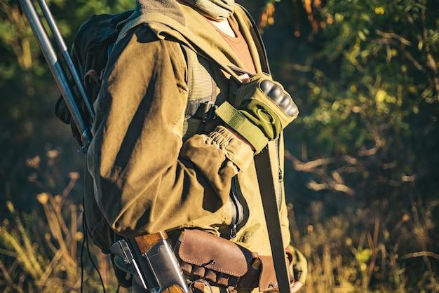 Myśliwy z strzelbą na polowaniu. myśliwy w kamuflażu gotowy do polowania z karabinem myśliwskim