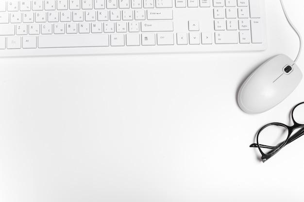 Mysz komputerowa, okulary i klawiatura