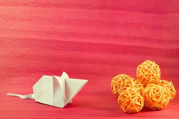 Mysz z białego papieru wykonana techniką origami patrzy na pomarańczowe kulki