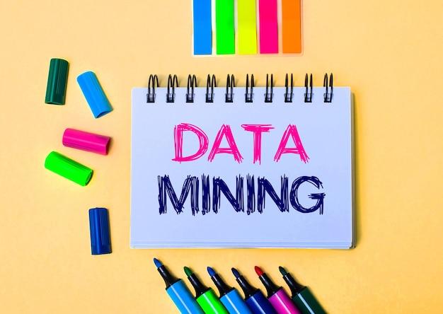Na beżowej powierzchni notes z napisem data mining, jasnymi pisakami i naklejkami