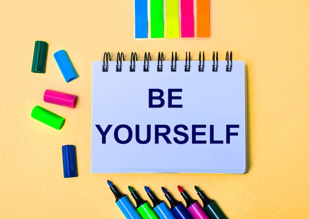 Na beżowej powierzchni zeszyt z napisem be yourself, jasnymi pisakami i naklejkami