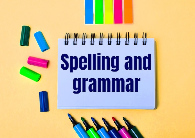 Na beżowej ścianie zeszyt z napisem spelling and grammar, jasnymi flamastrami i naklejkami