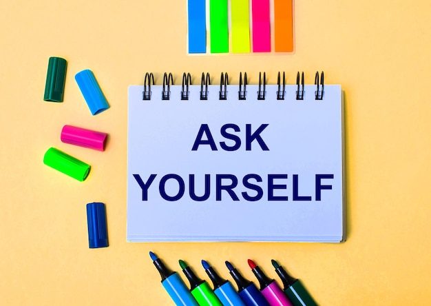 Na beżowym tle zeszyt z napisem ask yourself, jasnymi pisakami i naklejkami