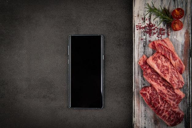 Na białej drewnianej mapie jest surowe mięso i telefon komórkowy