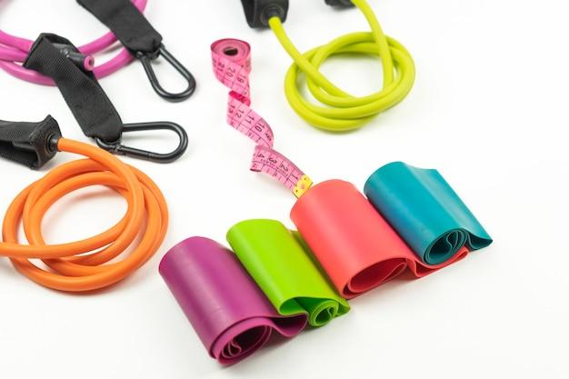 Na białej podłodze leżą kolorowe gumki fitness i ekspandery oraz różowa miarka