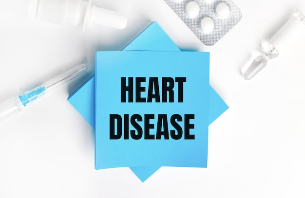 Na białej powierzchni strzykawka, ampułka, tabletki, fiolka z lekarstwem oraz jasnoniebieskie nalepki z napisem serce choroba