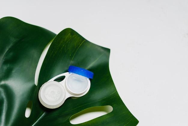 Na białej powierzchni zielony liść, na nim opakowanie na soczewki kontaktowe