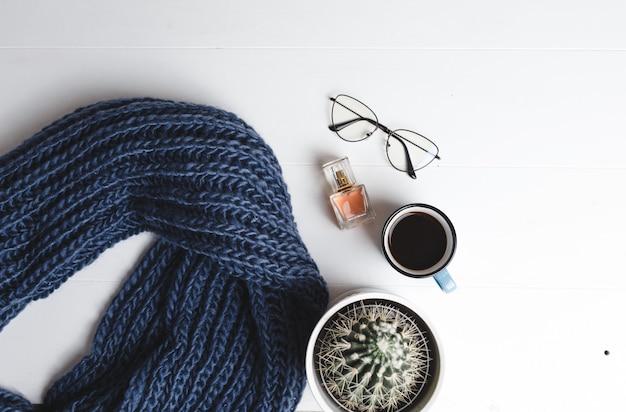 Na białej ścianie leży niebieski ciepły szal, filiżanka kawy, kaktus, okulary i damskie perfumy