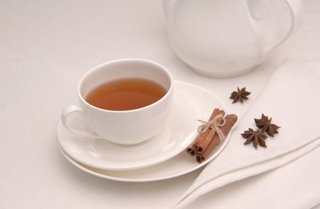 Na białej serwetce filiżanka herbaty na spodku i czajniczek i przyprawy