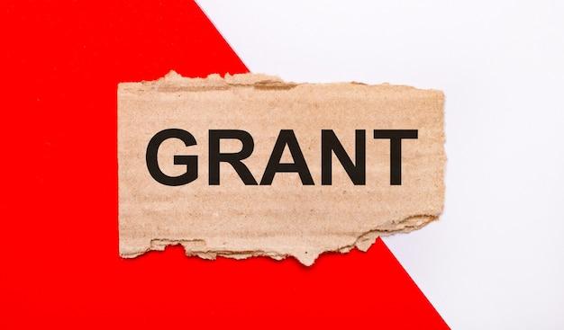 Na biało-czerwonym tle brązowy porwany karton z napisem grant