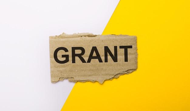 Na biało-żółtym tle brązowy porwany karton z napisem grant