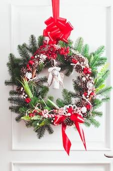 Na białych drzwiach wisi wieniec świąteczny. czerwono-białe elementy, kokardka do dekoracji domku letniskowego
