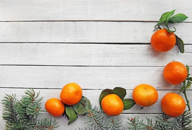 Na białym drewnianym tle leżą dojrzałe pomarańczowe mandarynki z liśćmi i iglastymi gałęziami jodły
